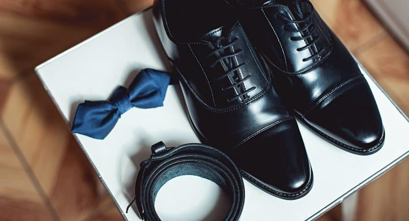 Close up of modern man accessories. black bowtie, leather shoes, and belt.
